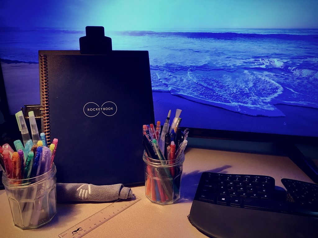 My pens of many colors with my journal and ocean view.